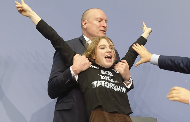 An activist is carried away after attacking ECB President Mario Draghi during a press conference of the European Central Bank, ECB, in Frankfurt, Germany, Wednesday, April 15, 2015. (AP Photo/Michael Probst) (Foto: AP)