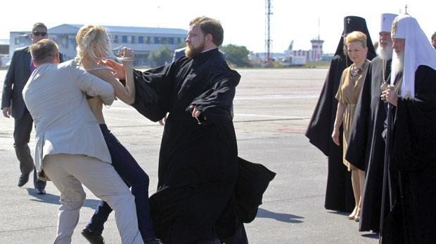 A topless activist of Ukraine women's movement Femen protesting against the visit of Russian Orthodox Church Patriarch Kirill (right) upon his arrival at the airport in Kyiv, Ukraine, yesterday.