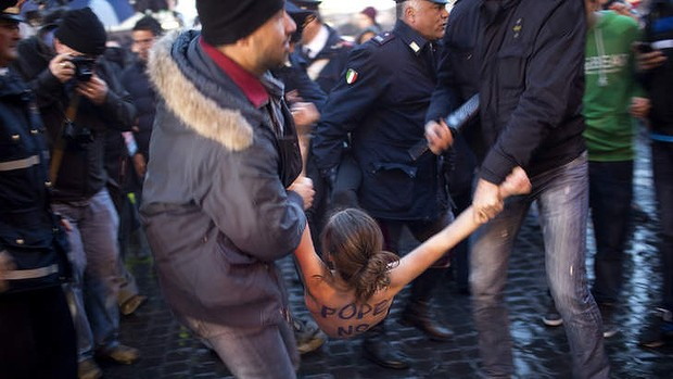 A Femen activist is detained by Italian police officers following a protest against the Pope while the papal conclave was sitting.