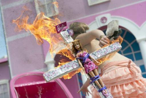 Militante do grupo Femen ateia fogo em boneca em protesto contra inauguração da casa da Barbie, em Berlim. Foto: Barbara Sax/AFP Photo