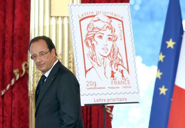 O presidente da França, François Hollande, apresenta o novo selo com imagem de Marianne, neste domingo (14), no Palácio do Eliseu, em Paris (Foto: AFP)