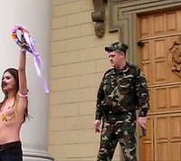 A Femen member demonstrates on the steps of the Belarus KGB headquarters in Minsk while an officer in fatigues watches on.
