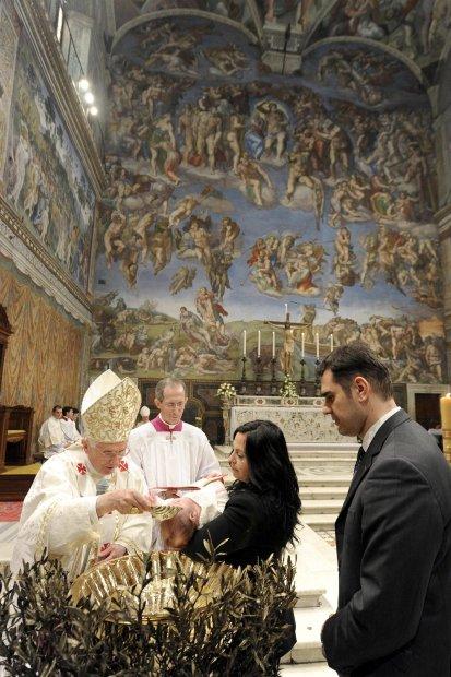 El papa Benedicto XVI bautiza a un niño en una ceremonia en la Capilla Sixtina, en el Vaticano, al conemorar el día del Bautismo del Señor