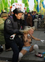 A Ukrainian police officer detains an activist from women's rights group Femen during an opposition rally in Kyiv