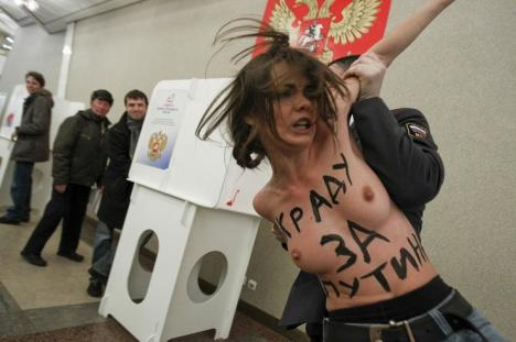 A policeman detains an activist of Ukrainian group Femen at a polling station in Moscow
