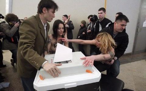 Οι ακτιβίστριες της FEMEN απομακρύνονται δια της βίας από το εκλογικό τμήμα.