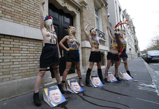 Com a calcinha abaixada, coroa de flores na cabeça, elas urinaram nas fotos do presidente aos gritos de 'Ucrânia na Europa' (AFP PHOTO / THOMAS SAMSON )