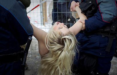 אחד המפגינות מובלת למעצר (צילום: AP)
