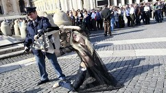 An activist from FEMEN holds up a sign in front of a police officer in Saint Peter's Square in Vatican City