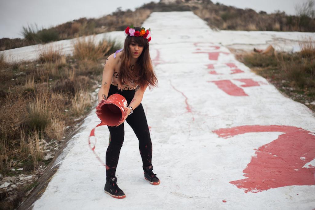 Lara, líder del movimiento Femen en España, arrojando el sobrante de pintura tras realizar la pintada. / A. M. V.