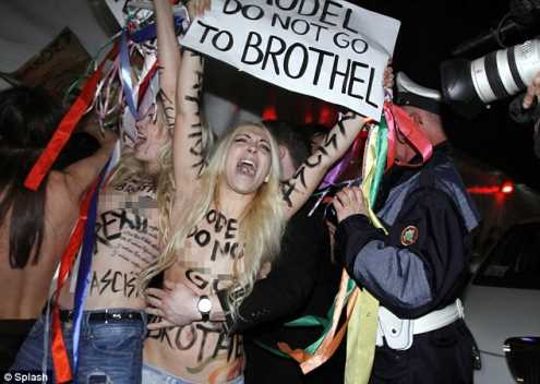 上空抗議民眾被阻擋在時裝秀展場外。(圖/翻攝自每日郵報)