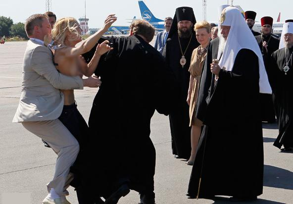 A topless protester is stopped from attacking Patriarch Kirill in Kyiv.