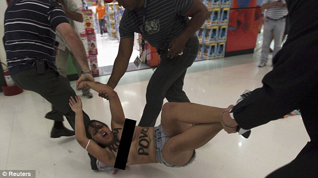 An activist from women's rights group Femen is arrested by security guards during a protest in a shopping mall, in Sao Paulo, Brazil
