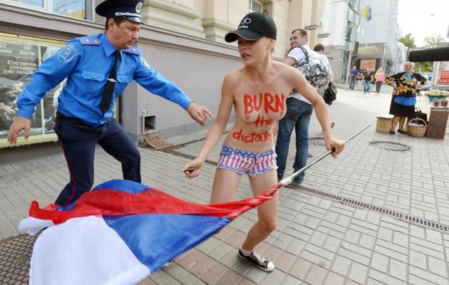 Un officier de police tente d'arrêter une Femen, le 18 juillet 2013 à Kyiv [Genya Savilov / AFP/Archives]