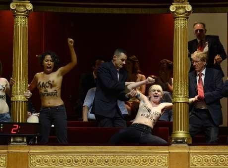 Tres activistas de la organizacin feminista Femen protestaron hoy con los senos al descubierto en el Senado francs contra una modificacin del proyecto de ley sobre la prostitucin en fase de tramitacin que anula la penalizacin de los clientes. Las tres mujeres, que se encontraban en las gradas del pblico de la cmara alta francesa, se descubrieron los senos en los que haban escrito mensajes contra los senadores que han decidido suprimir las disposiciones que castigaban a los clientes de las prostitutas. Foto: AFP