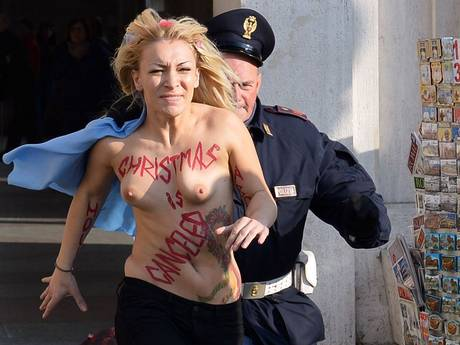 Inna Shevchenko, leader of the Ukrainian feminist protest group Femen is chased by a policeman outside Saint Peter's Square in the Vatican. Femen activists started an international topless marathon to protest against the Catholic church's views on abortion