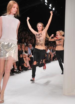 A modelo inglesa Hollie-May Saker desfila enquanto as ativistas invadem a passarela (Foto: Dominique Charriau/Getty Images)