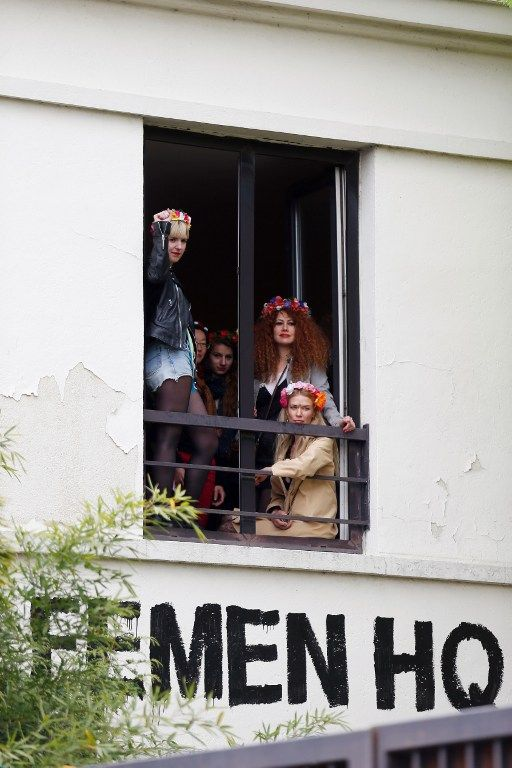 Ukrainian feminist protest group Femen militants gather at the window of their new French headquarters during its inauguration in Clichy, near Paris, on April 19, 2014. AFP PHOTO / THOMAS SAMSON