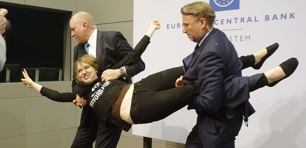 A Femen activist is carried away after attacking ECB President Mario Draghi during a press conference of the European Central Bank, ECB, in Frankfurt, Germany, Wednesday, April 15, 2015. (AP Photo/Michael Probst) (Foto: AP)