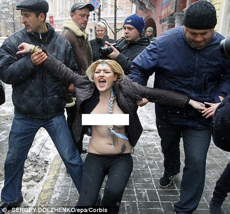 Ukrainian policemen arrest one of the activists protesting in Kyiv