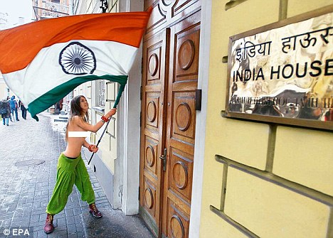 A topless Femen activist uses a Tricolour to beat at the door of the Indian envoy¿s residence in Kyiv