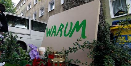Ein Schild mit der Aufschrift Warum steht an einem Baum in der Straße, wo am Freitag drei Kinder getötet wurden (Quelle: dapd)