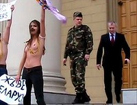 Members of Femen demonstrate on the steps of the Belarus KGB headquarters in Minsk, while officials watch on.