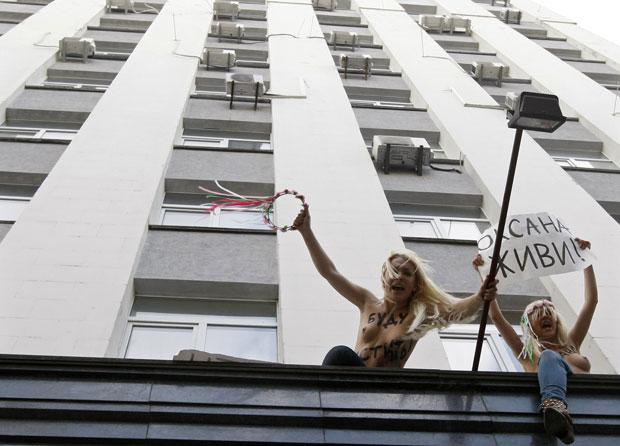 As feministas subiram na fachada do prédio para protestar com cartazes e pinturas no corpo (Foto: Anatolii Stepanov/Reuters)