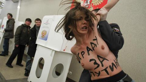 ANGREP PUTINS STEMMELOKALER: Her blir en demonstrant pågrepet av en politimann under demonstrasjonen i det samme stemmelokalet der statsminister Vladimir Putin stemte. Foto: Reuters/Denis Sinyakov/Scanpix