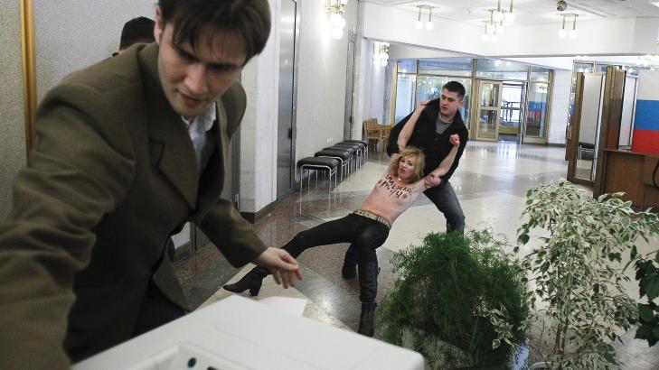 KREML-RÅTTER: Her drar en sikkerhetsvakt en av aktivistene bort fra stemmeboksene ved et stemmelokale i Moskva. På brystene hennes har hun skrevet Kreml-rotter. Foto: Reuters/Denis Sinyakov/Scanpix