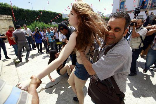 Des policiers tunisiens interpellent une militante Femen, le 29 mai à Tunis, lors d'un rassemblement de soutien à Amina Sbouï devant le ministère de la justice.