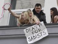 """Auch Aktivistinnen der ukrainischen Aktions-Gruppe """"Femen"""" beteiligten sich an den Protesten. Auf einem Plakat fordern sie: """"Tod den Sadisten"""""""