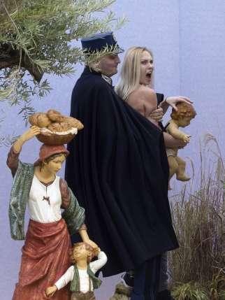 Femen-Aktivistin hält brüllend den Jesus im Arm.
