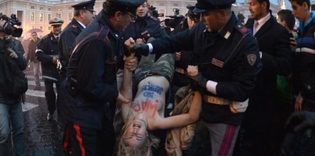 Une Femen est vacue de la place Saint-Pierre, le 12 mars. (AFP PHOTO / GABRIEL BOUYS)