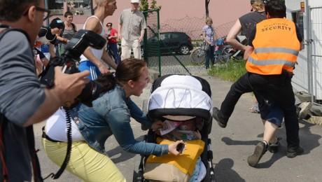 Rangelei: Eine Mutter rettet ihr Baby aus dem umstürzenden Kinderwagen. Hinten: Security-Mitarbeiter und Demonstrant