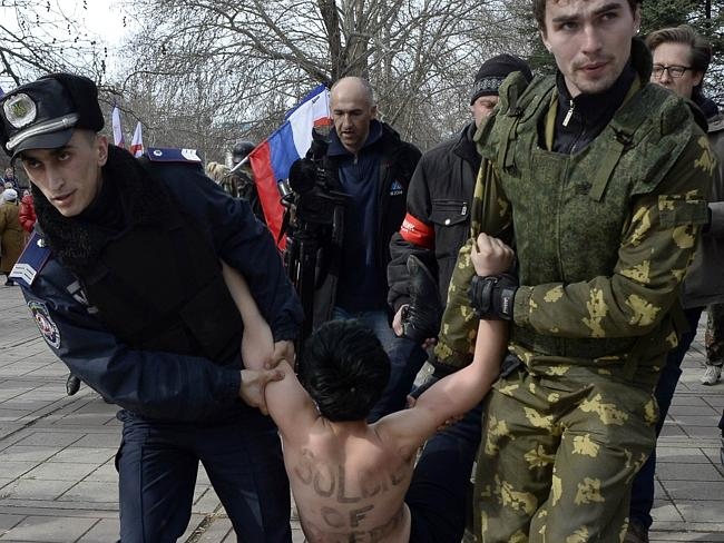 A Ukrainian police officer (L) and a pro-Russian volunteer (R) detain a topless activist