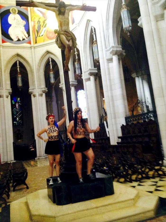 Dos activistas de Femem, Con el lema libertad para abortar pintado con tinta negra en su cuerpo, se han encadenado a un crucifijo en el altar de la catedral de la Almudena, en Madrid, para reivindicar el derecho al aborto libre de las mujeres. EFE
