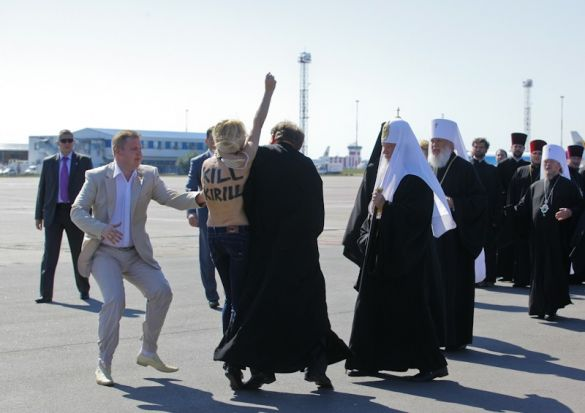 A cleric blocking Femen activist Yana Zhdanova from reaching Patriarch Kirill. Zhdanova was sentenced Friday to 15 days' administrative arrest for the topless protest.