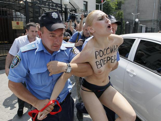 Un policía arresta a una activista semidesnuda del grupo radical feminista Femen durante una protesta contra el presidente ruso, Vladímir Putin, por el anuncio de su divorcio, frente a la embajada de Rusia en Kyiv, Ucrania. Foto: EFE en español