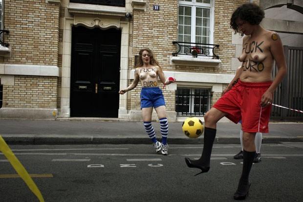 Com os seios à mostra, mulheres do Femen protestam com bola de futebol em Paris (Foto: Guillaume Baptiste/AFP)