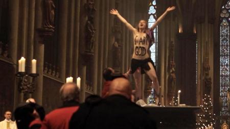 Nackt auf dem Altar des Kölner Doms am Heiligabend: Eine Femen-Aktivistin hat die Christmesse gestürmt (Quelle: Elke Lehrenkrauss/dpa)