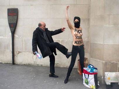 Feminista de Femen es pateada por un transeúnte. Foto: AFP