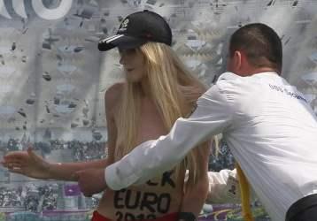 In topless, la ragazza si avvicina alla coppa con la scritta Fuck Euro 2012 sulla pancia