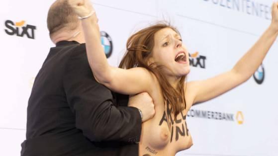Ein Leibwchter drngt am Donnerstagabend eine Femen-Aktivistin vom blauen Teppich