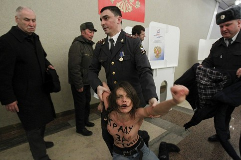 Policemen detain an activist of Ukrainian group Femen at a polling station in Moscow