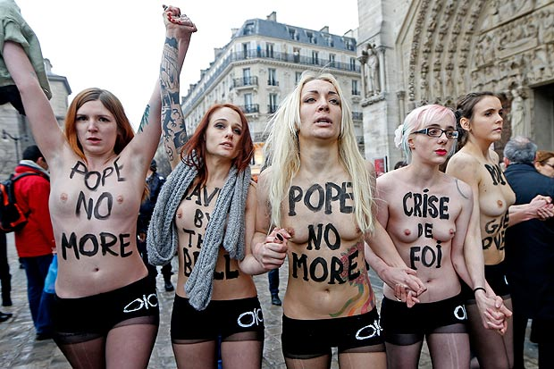 Topless protesters join hands as they march through Paris