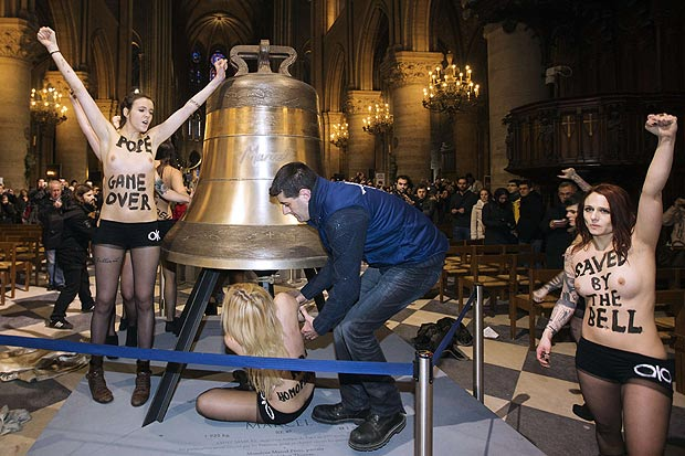 Staff drag a protester away as she rings the giant bell inside the Notre Dame