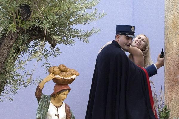 A gendarme from the Vatican's security forces stops a Ukrainian feminist group Femen activist after she snatched the statue of Baby Jesus from the Nativity scene set in St. Peter's Square at the Vatican, Thursday, Dec. 25, 2014. AP