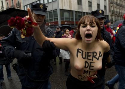 Una activista de Femen, rodeada de policías, en una marcha antiaborto.