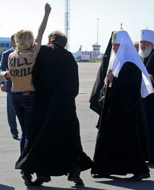 A Femen activist targets Russian Orthodox Patriarch Kirill at Kyiv airport. (File, AP)